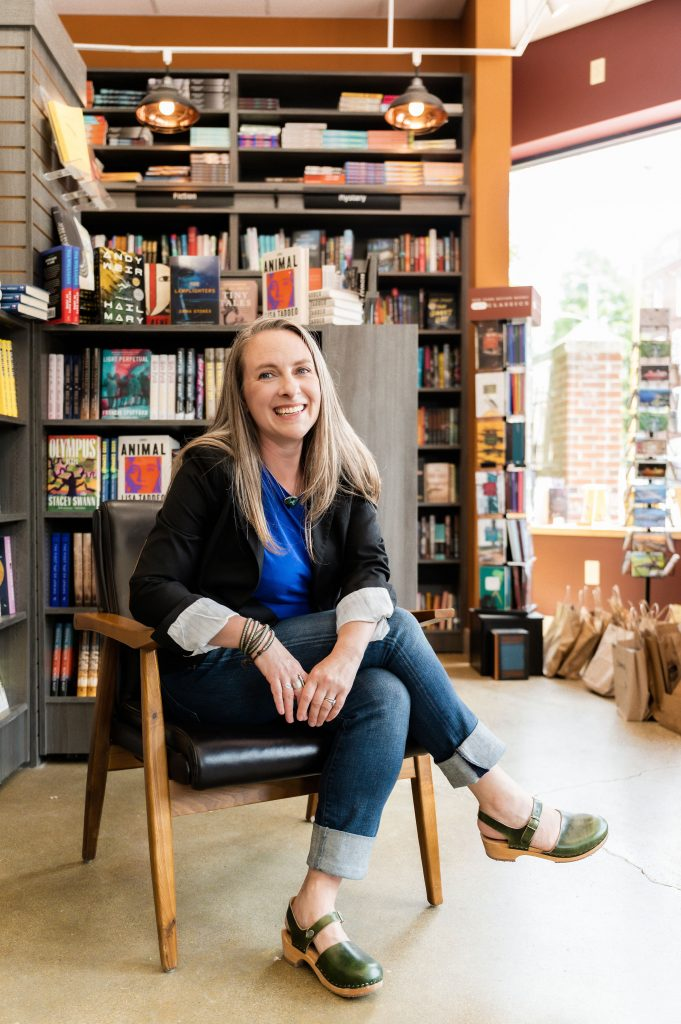 Photo of Julie Falatko, sitting in a chair in Print: A Bookstore in Portland, Maine. Photo by Elle Darcy.